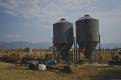 在老生锈的农场的两种金属筒仓 免版税库存图片