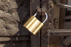 在老生锈的酒吧的新的锁 免版税图库摄影