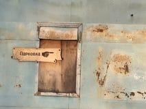 在老生锈的金属墙壁上的标志 免版税图库摄影