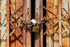 在老生锈的铁门的老生锈的挂锁 免版税图库摄影
