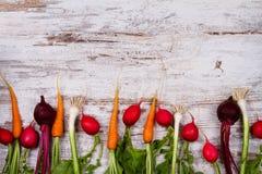 在老白色书桌上的菜:嫩胡萝卜,大蒜,甜菜根,萝卜 免版税库存照片