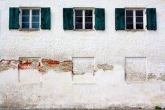 在老白色墙壁上的三个老窗口作为背景 免版税图库摄影