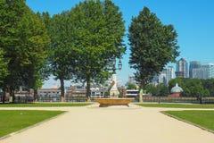 在老皇家海军学院附近的一个喷泉在格林威治,有金丝雀码头摩天大楼的伦敦在背景中在夏天 免版税库存图片