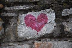 在老石墙上的红色心脏 免版税库存照片