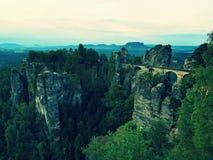 在老石桥梁的早晨在夏天结束时 秋天风景,在天际的破晓 萨克森瑞士,德国 库存照片