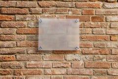 在老砖墙上的空的信息标志 库存图片