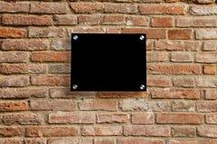 在老砖墙上的空的信息标志 免版税库存照片