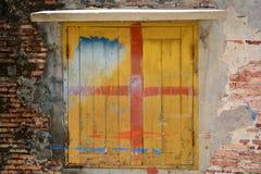 在老砖墙上的破裂的混凝土有窗口的 库存图片
