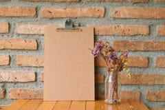 在老砖墙和花附近的空白的剪贴板 免版税库存图片
