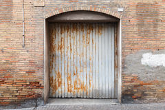 在老砖墙的生锈的脏的金属门 免版税库存照片