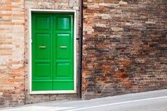 在老砖墙的绿色木门 免版税库存照片
