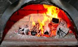 在老砖壁炉的火焰状木头 免版税库存照片