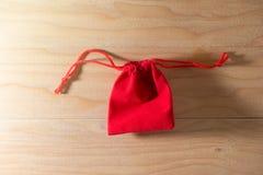 在老破旧的木表概念圣诞节和Newyear的红色礼物袋子 免版税图库摄影