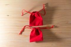 在老破旧的木表概念圣诞节和Newyear的红色礼物袋子 免版税库存图片