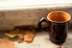 在老窗台的咖啡杯与黄色叶子 免版税图库摄影