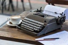 在老笔纤管滚动葡萄酒文字黄色附近仍然登记概念生活 减速火箭的打字机和一个杯子热奶咖啡 图库摄影