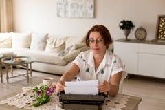 在老笔纤管滚动葡萄酒文字黄色附近仍然登记概念生活 工作使用她减速火箭的女性作者打字 库存图片