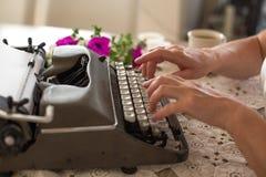 在老笔纤管滚动葡萄酒文字黄色附近仍然登记概念生活 键入在减速火箭的打字机的手 免版税库存图片