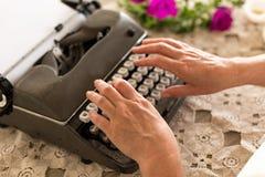 在老笔纤管滚动葡萄酒文字黄色附近仍然登记概念生活 键入在减速火箭的打字机的手 库存照片