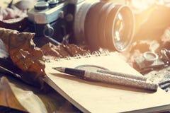 在老笔记本的减速火箭的在干燥叶子的笔和照相机在密林背景中 库存照片