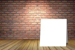 在老红砖墙壁中空的室的白色卡片  透视棕色木地板 从上面的斑点光 对显示礼物产品 免版税库存照片
