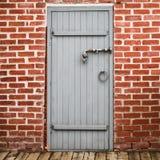 在老红砖墙壁的灰色木门 免版税库存照片