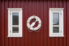 在老红色木墙壁上的救生圈 库存照片
