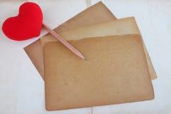 在老纸和铅笔的红色心脏 库存图片