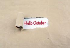 在老纸显露的题字-你好10月 免版税图库摄影