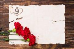 在老纸概念板料的三支红色康乃馨  库存图片