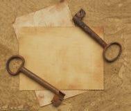 在老纸的两把生锈的钥匙 库存照片