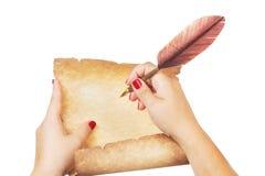 在老纸纸卷和钢笔的女性手文字有在白色背景隔绝的羽毛纤管的 库存图片