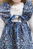 在老纺织品的玩偶编织了有嫩花卉图案的蓝色礼服 免版税库存照片