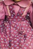 在老纺织品的玩偶编织了有蓝色花卉图案的红色礼服 库存图片