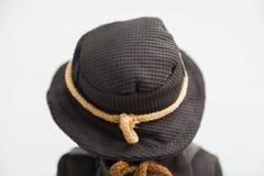 在老纺织品的玩偶编织了有嫩花卉图案的棕色礼服 免版税库存图片