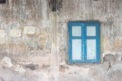 在老肮脏的墙壁上的天蓝色窗口 图库摄影