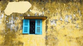 在老肮脏的墙壁上的蓝色窗口 免版税库存照片