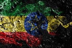 在老肮脏的墙壁背景的埃塞俄比亚发烟性神秘的旗子 皇族释放例证