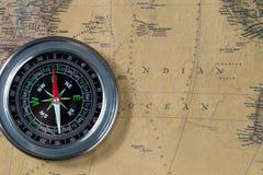 在老葡萄酒地图,印度洋,宏观背景的黑指南针 免版税库存照片