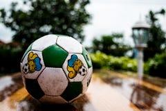 在老葡萄酒木桌上的足球橄榄球有棕褐色的背景 库存图片