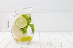 在老葡萄酒木桌的刷新的自创石灰和薄菏鸡尾酒 戒毒所果子灌输了调味的水 干净吃 免版税库存图片
