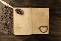 在老葡萄酒的咖啡豆打开书 菜单,食谱,嘲笑 木背景 免版税图库摄影
