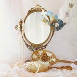 在老葡萄酒长圆形镜子旁边的蓝色威尼斯式面具 库存照片