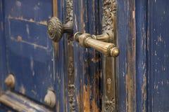 在老蓝色前门的黄铜门把手 图库摄影
