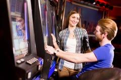 在老虎机的年轻夫妇在赌博娱乐场 免版税库存图片