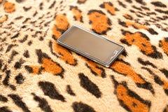 在老虎皮肤背景的黑智能手机  库存照片