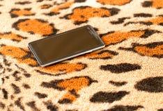 在老虎皮肤背景的黑智能手机  图库摄影