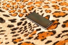 在老虎皮肤背景的黑智能手机  免版税库存图片