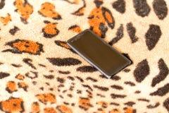 在老虎皮肤背景的黑智能手机  免版税库存照片