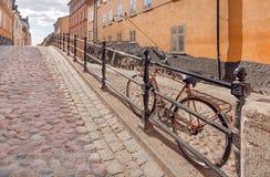 在老街道上的Bycicle有被修补的石头和五颜六色的历史房子的 斯德哥尔摩,瑞典都市风景  库存照片